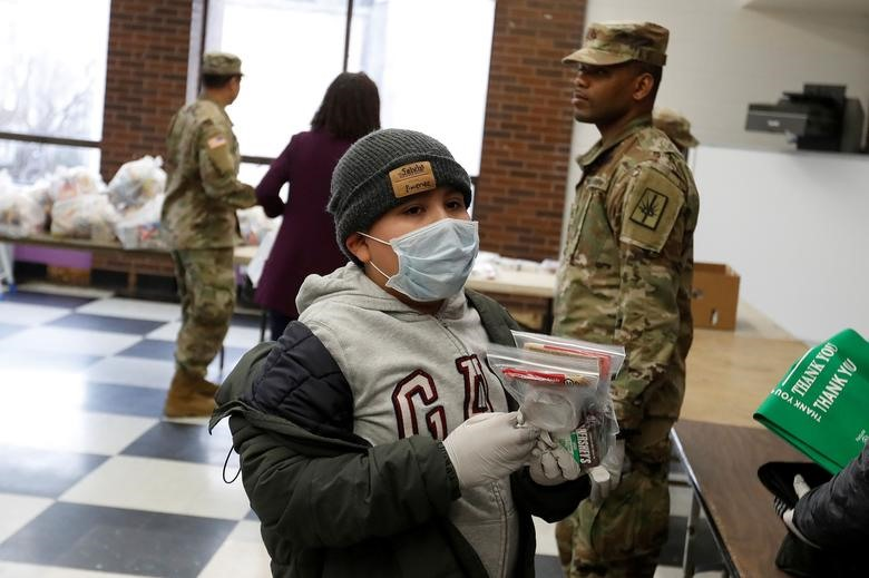 Selvin Jimenez, 10, receives food donations from the National Guard in New Rochelle, New York, March 12, 2020. National Guard troops delivered groceries and other necessities to the more than 100 people who were ordered to stay in their houses after testing positive for the coronavirus. REUTERS/Shannon Stapleton
