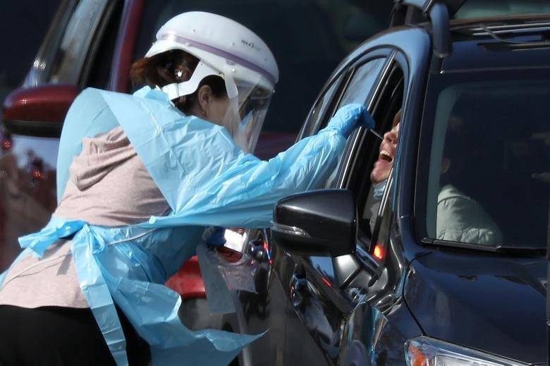 A health care worker tests people at a drive-thru testing station run by the state health department, for people who suspect they have novel coronavirus, in Denver, Colorado, March 11, 2020. REUTERS