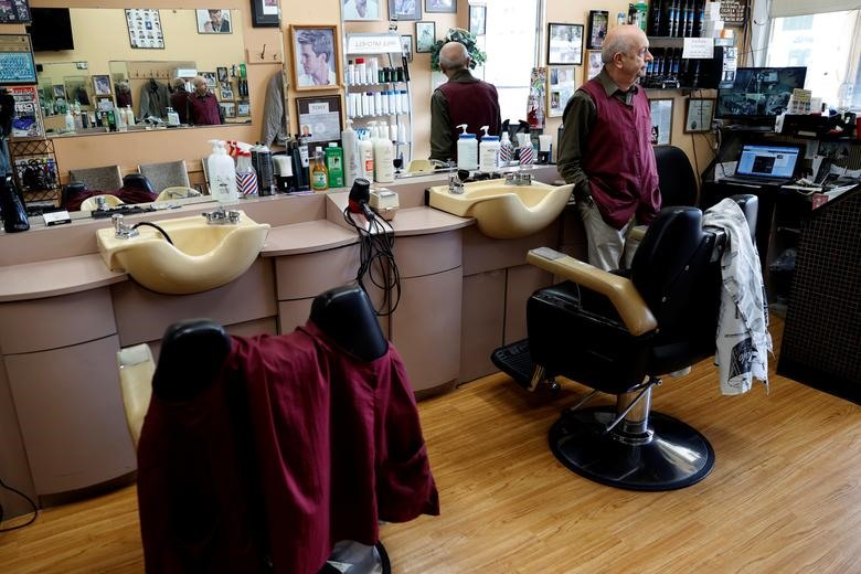 Owner Pino D'erasmo, the Owner of Pino's Hair Salon looks out from his empty shop during the coronavirus outbreak on North Avenue in New Rochelle, New York, March 11, 2020. REUTERS/Mike Segar