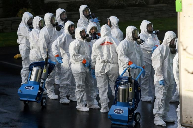 Members of a Servpro cleanup crew wearing hazardous material suits prepare to enter Life Care Center of Kirkland, the Seattle-area nursing home at the epicenter of one of the biggest coronavirus outbreaks in the United States, in Kirkland, Washington, March 11, 2020. REUTERS/Jason Redmond