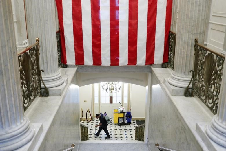 An Architect of the Capitol staff member vacuums the floor beneath an American Flag on Capitol Hill in Washington, March 12, 2020. REUTERS/Tom Brenner